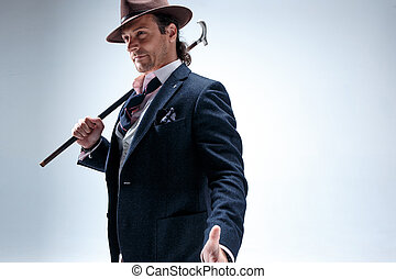 The mature man in a suit and hat holding cane. - The mature...