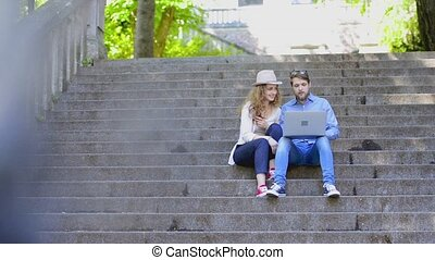 Couple with laptop sitting on stairs in town talking. -...