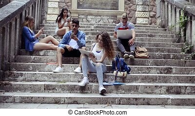 Teenage students with gadgets outside on stone steps. -...