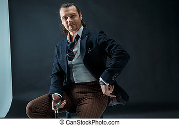 Businessman sitting on an armchair - The mature stylish man...