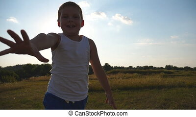 Happy little boy with an outstretched hand running at field behind camera and trying to catch it. Smiling male kid having fun in nature on sunny day. Child jogging outdoor. Slow motion Close up