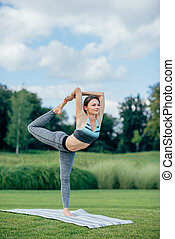 fit woman performing yoga - side view of smiling fit woman...