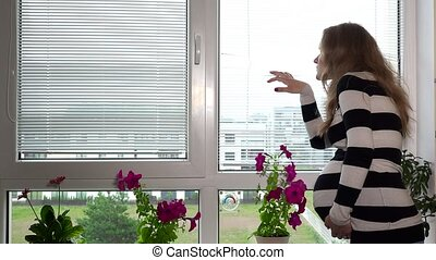 pregnant woman looking through window blinds louver. Static...