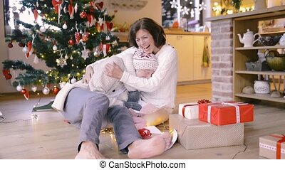 Senior couple in front of Christmas tree enjoying presents....