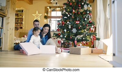 Young family with daugter at Christmas tree at home. -...