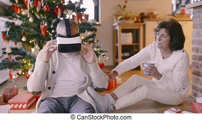 Senior couple in front of Christmas tree with VR goggles. -...