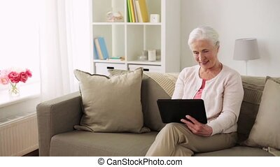 happy senior woman with tablet pc at home - technology, old...