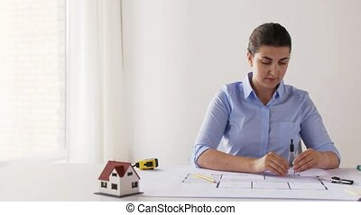 female architect with compass measuring blueprint -...