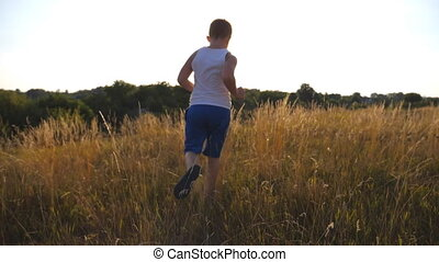 Following to young boy running on green grass at the field...