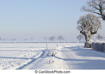 snow covered road - a winter landscape with a small country...