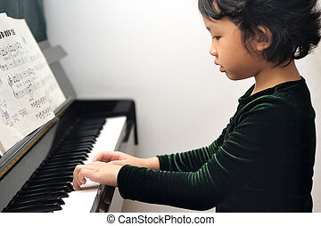 Asian kid playing piano - Asian kid learning to play piano