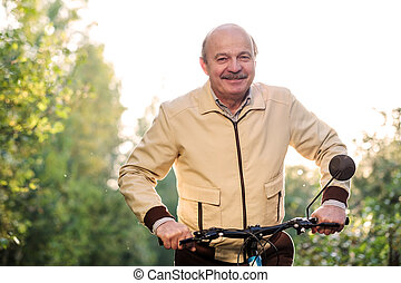 Senior man on cycle ride in countryside - Senior caucasian...