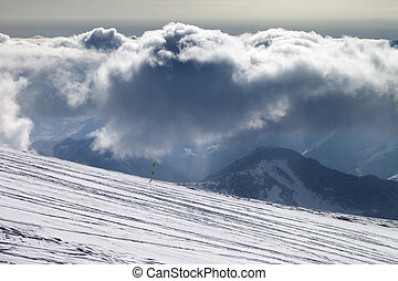 Ski slope for slalom and sunlight storm clouds with falling...