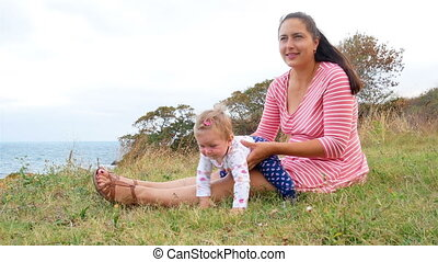 Mother and daughter are sitting on the beach playing. Happy...