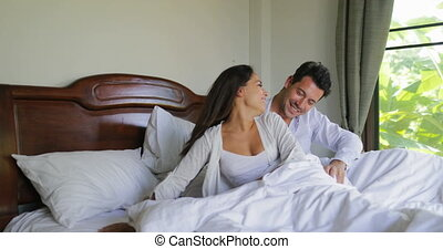 Young Couple Waking Up In Bed Stretching Arms, Beautiful...