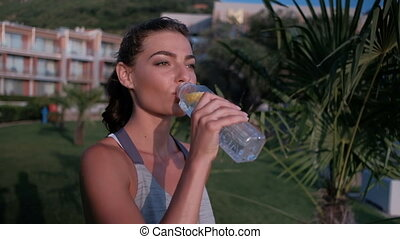 Young woman drinking water standing on green lawn on summer...