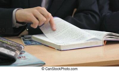 Schoolboy flips pages of school book. Close up - Schoolboy...