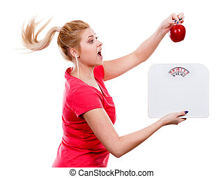 Woman holding apple and weight machine - Healthy fit...