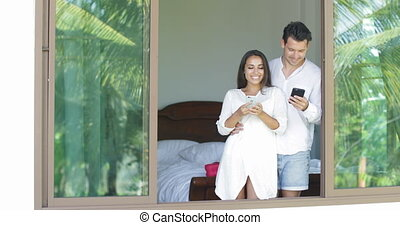 Young Couple Use Cell Smart Phones Talking Looking In Window...