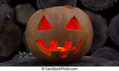 Jack-o-lantern with fire inside flickers lying on a stump -...