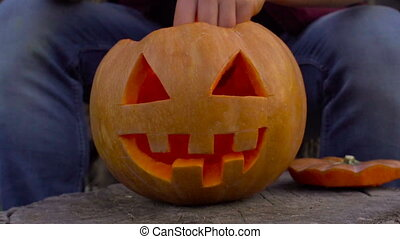 A man puts a burning candle in Jack's Lantern. In the backyard on the stump