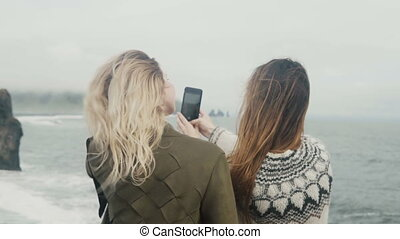 Two happy women taking selfie photos on smartphone, girls...