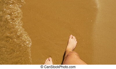 Men's feet on sandy beach into sea wave, point of view.