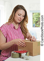 Woman At Home Writing Address On Package