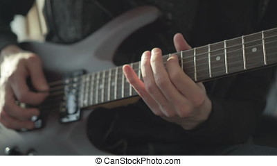 Man Playing on an Electric Guitar - Detailed view of a man...