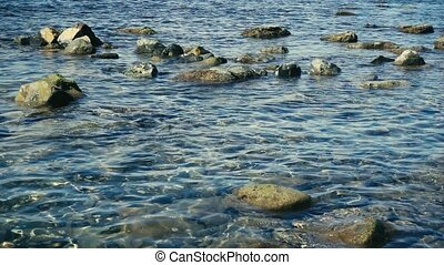 Crystal clear water on a stony shore slow motion - A small...