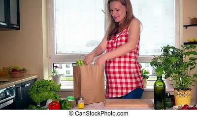 Smiling pregnant wife unload shopping bag with organic...
