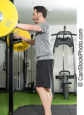 Man Standing By a Barbell Safety Stand in Gym