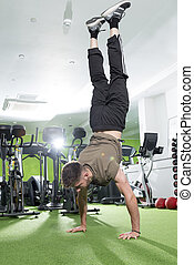 Young Man Doing a Hand Stand in a Gym - Young man doing a...