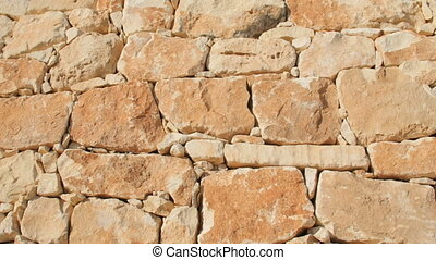 A fragment of a yellow stone wall on a blue sky background
