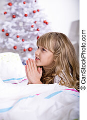 xmas praying - a little girl waking up in front of Christmas...