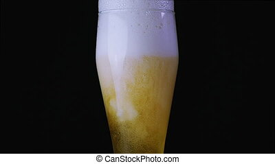 Beer is poured into the glass on a black background. Foam...