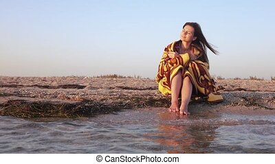 Girl in plaid by sea - At dawn the girl is wrapped in a...