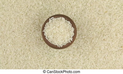 Rotation and approaching of rice in a clay pot, standing on...