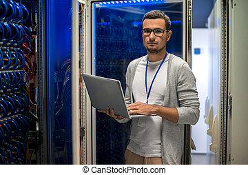 Network Engineer Managing Servers - Portrait of young man...