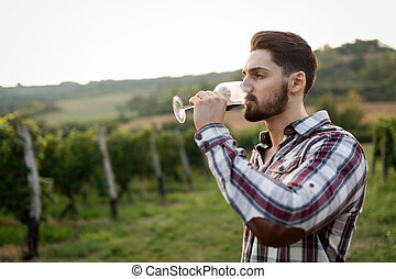 Winegrower tasting wine in vineyard - Happy winegrower...