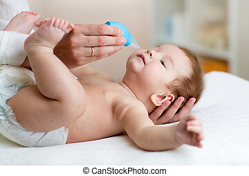 Mother or doctor cleans baby's nose with blower, while...
