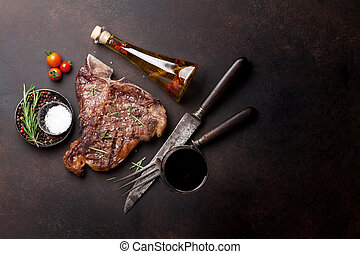 T-bone steak - Grilled T-bone steak and red wine glass on...