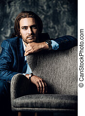 man by the chair - Vogue shot of a handsome man sitting near...