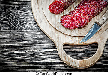 Chopped salami knife on wooden carving board.