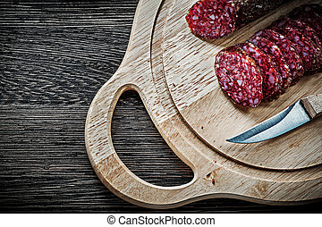 Sliced salami knife on wooden carving board.