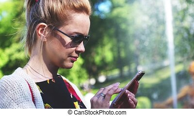 Woman in the park with a smartphone writes a message on her...