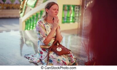 Young sad woman coming in temple prays on the knees at...
