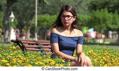 Pretty Teen Girl Sitting In Park With Butterfly