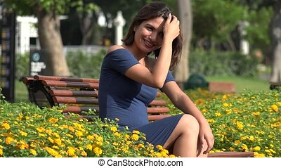 Happy Female Teen Sitting In Park