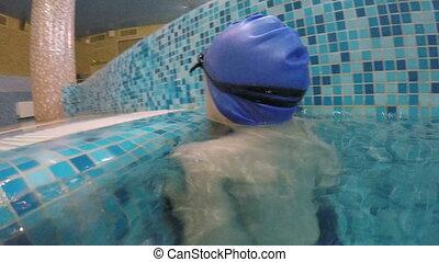 Happy kid bathing in the pool